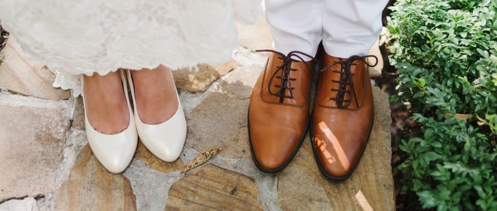 bride in white shoes and groom in brown shoes